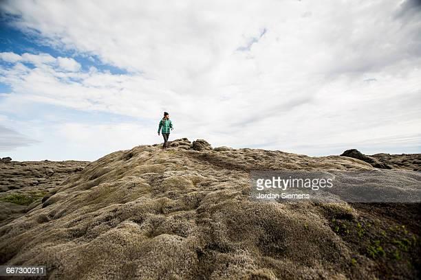 A woman hiking across mossy lava rock.