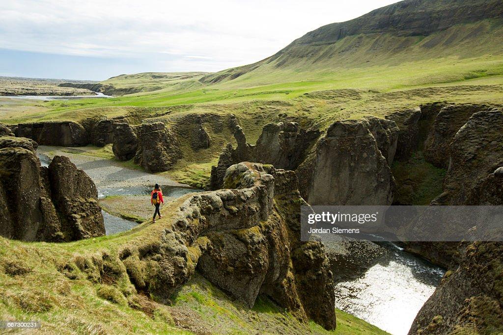 A woman hiking across mossy lava rock. : Stock-Foto