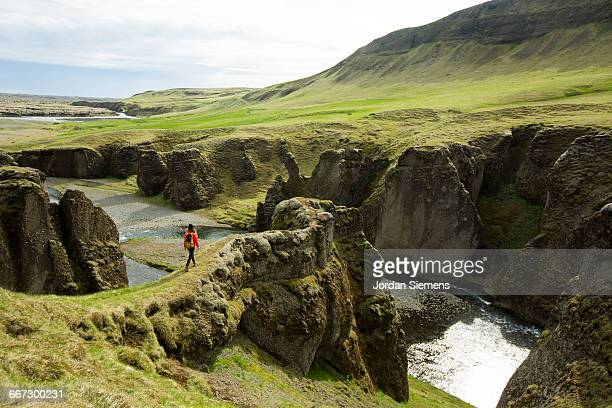 a woman hiking across mossy lava rock. - reykjavik stock pictures, royalty-free photos & images