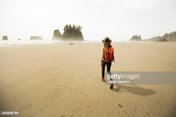 a woman hiking along a remote beach. - donna di spalle al mare foto e immagini stock