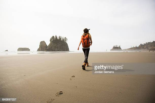 a woman hiking along a remote beach. - wonderlust stock pictures, royalty-free photos & images
