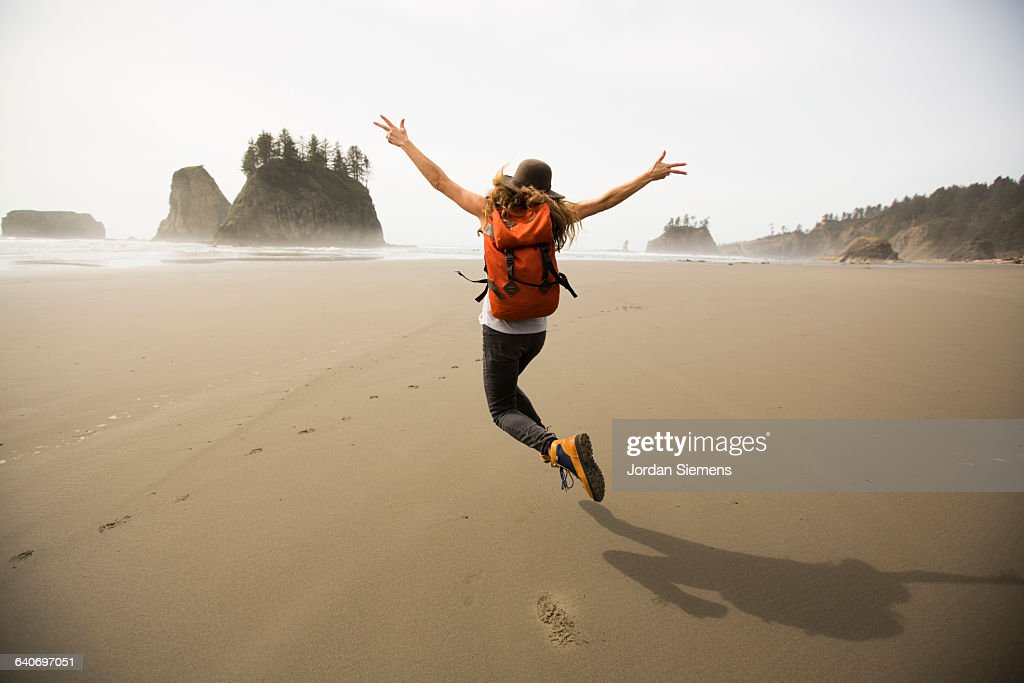 A woman hiking along a remote beach. : Stock Photo