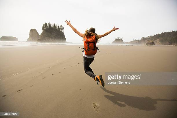 a woman hiking along a remote beach. - alegria imagens e fotografias de stock