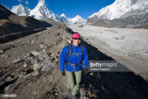 woman hiking along lateral moraine above khumbu glacier as clouds rest above summit of mt pumori in distance, khumbu region. - vista lateral stock pictures, royalty-free photos & images