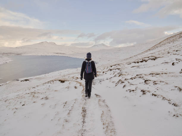 Woman hiking along snow path near Leitisvatn lake in the Faroe Islands