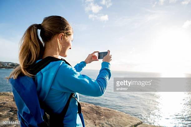 woman hiking and taking a picture of the sunset