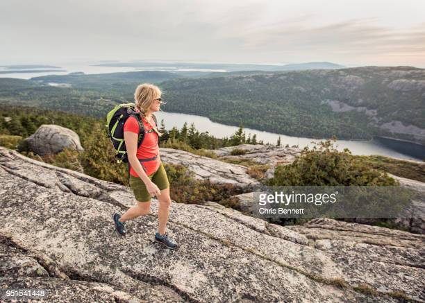Woman hiking at summit of Pemetic Mountain, Acadia National Park, Maine, USA