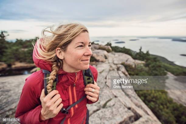 woman hiking at summit of pemetic mountain, acadia national park, maine, usa - buitensport stockfoto's en -beelden