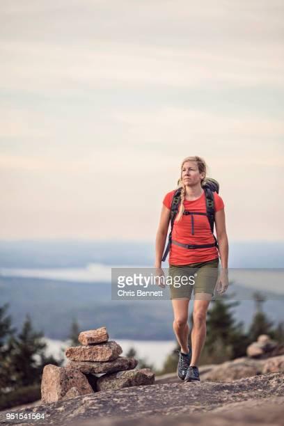 woman hiking at summit of pemetic mountain, acadia national park, maine, usa - shorts stock-fotos und bilder