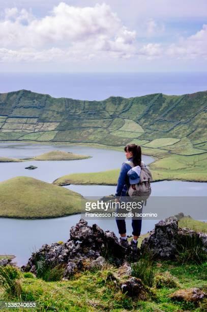 woman hiking at volcanic crater caldeirao, corvo island near flores, azores, portugal - iacomino portugal foto e immagini stock