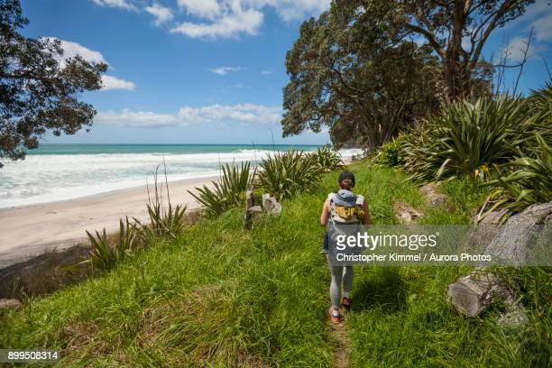 Woman hiking at Waihi Beach in Orokawa Scenic Reserve, New Zealand