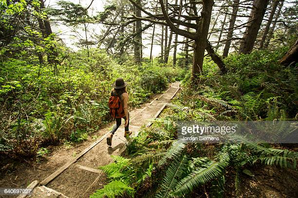 A woman hiking in a dense forest.