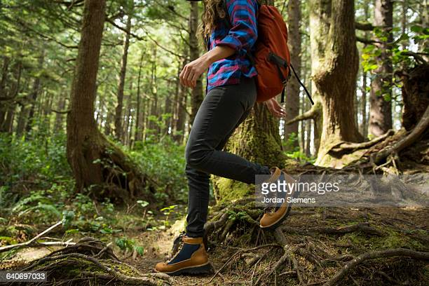 a woman hiking in a dense forest. - stiefel stock-fotos und bilder