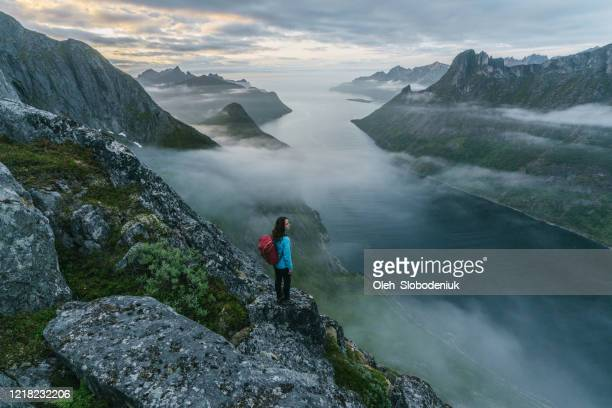 woman hiking  in mountains  on senja island in fog - norway stock pictures, royalty-free photos & images