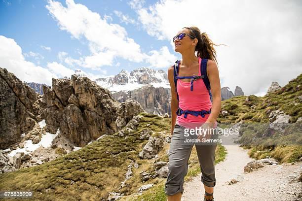 a woman hiking in the mountains. - pantaloni foto e immagini stock