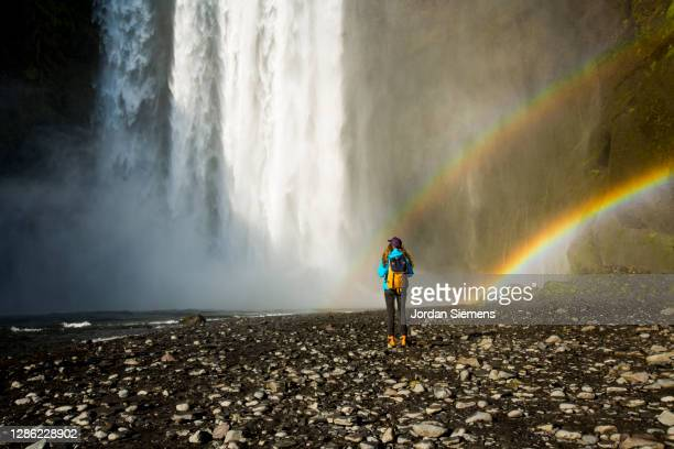 a woman hiking near skógafoss waterfall in iceland. - iceland stock pictures, royalty-free photos & images
