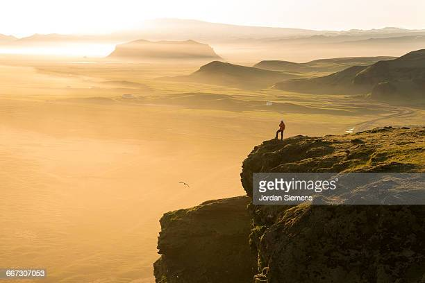 a woman hiking on a high cliff - dramatic landscape stock pictures, royalty-free photos & images