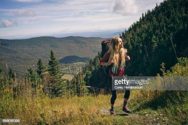 Woman hiking on a rocky ridgeline in New England.