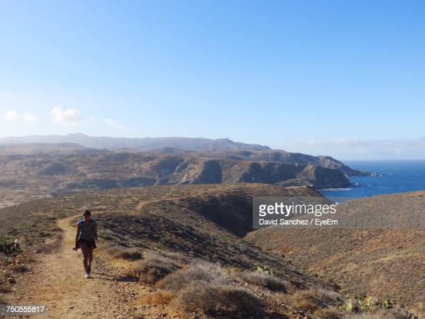woman hiking on mountain at santa catalina island against blue sky - catalina island stock photos and pictures