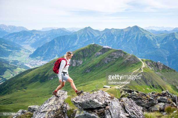 woman hiking on mountain path above gastein, salzburg, austria - salzburg stock pictures, royalty-free photos & images