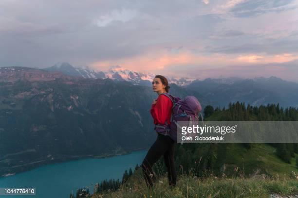 Woman hiking on the mountain ridge in Swiss Alps