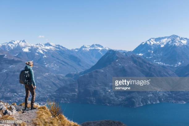 woman hiking on top of the hill over lake - patagonia foto e immagini stock