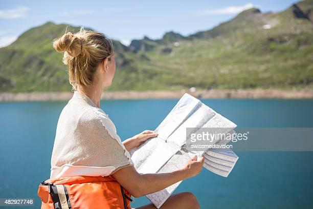 Femme randonnées assis sur rocher de la recherche de randonnée sur la carte