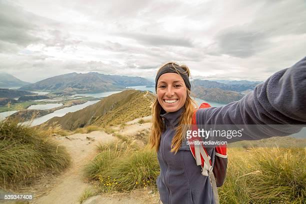Woman hiking takes selfie on mountain top