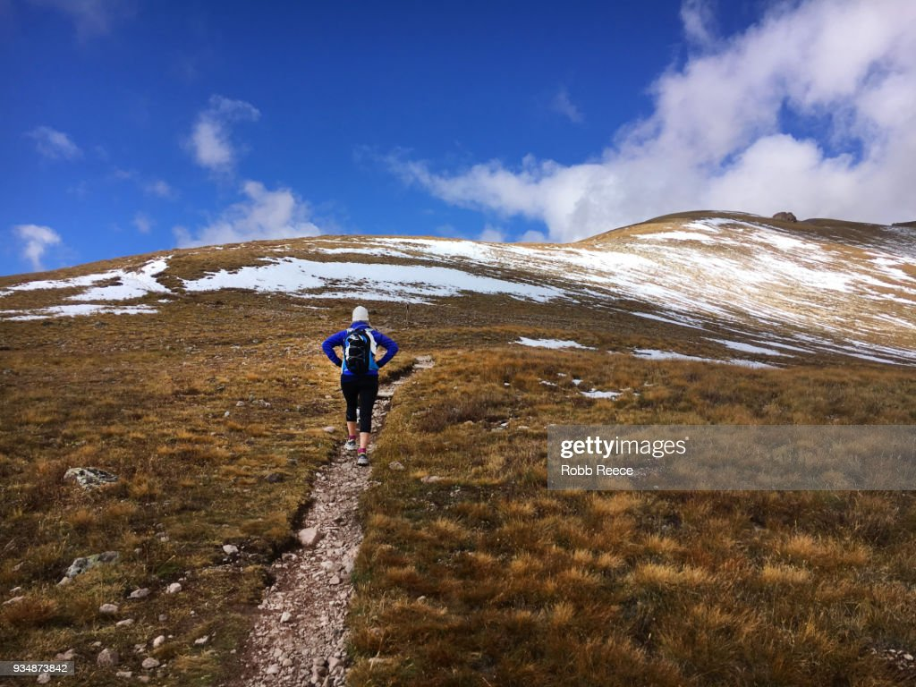 A woman hiking uphill on a remote mountain trail : Stock Photo