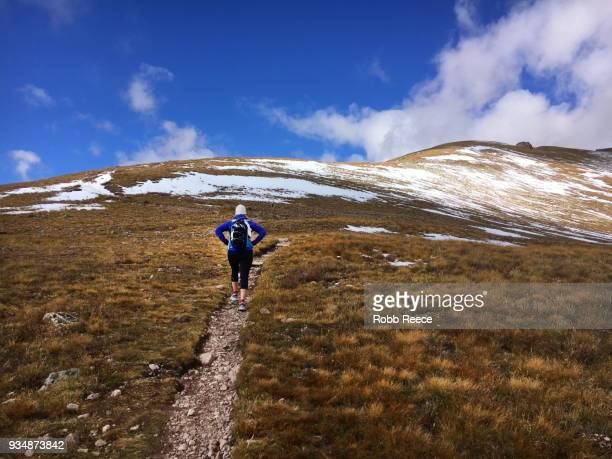 a woman hiking uphill on a remote mountain trail - robb reece stock pictures, royalty-free photos & images