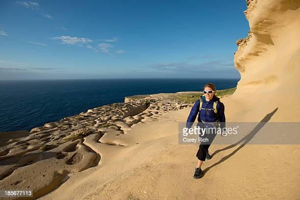 A woman hiking while on a climbing trip in Malta.