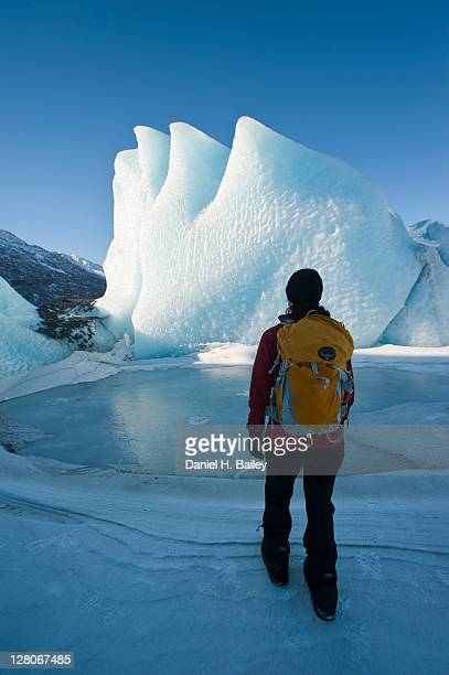 Woman hiking with a backpack in front of an ice formation on the Knik Glacier, winter, Chugach Mountains, Alaska, USA, March 2011
