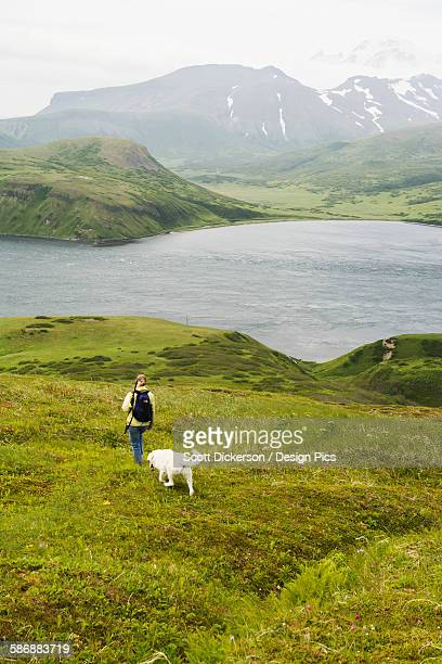 A Woman Hiking With Her Dog And Enjoying The View Of Isanotski Strait In False Pass, From Unimak Islands Eastern Shore