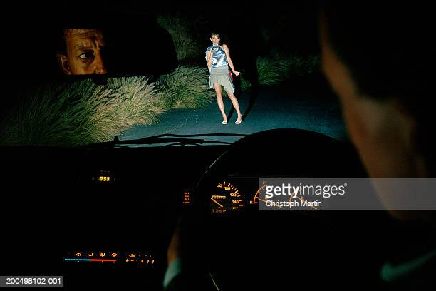 Woman hitch hiking at night, seen from car interior