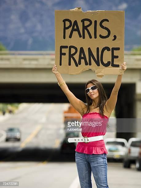 Woman hitchhiking a ride to Paris