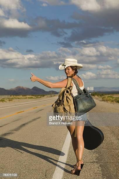 Woman hitchhiking along highway