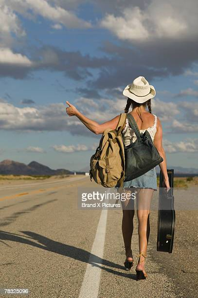 Woman hitchhiking along lonesome road