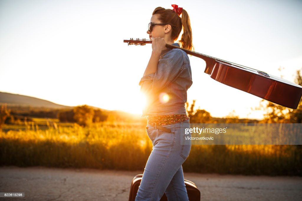 Woman hitchhiking on road : Stock Photo