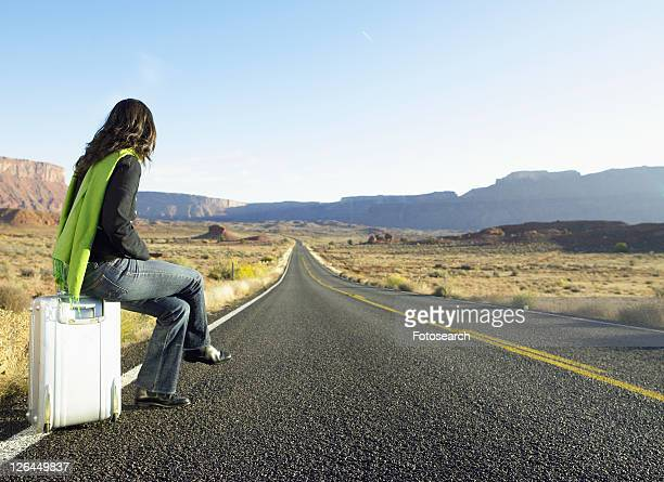 Woman hitchhiking on rural road, rear view