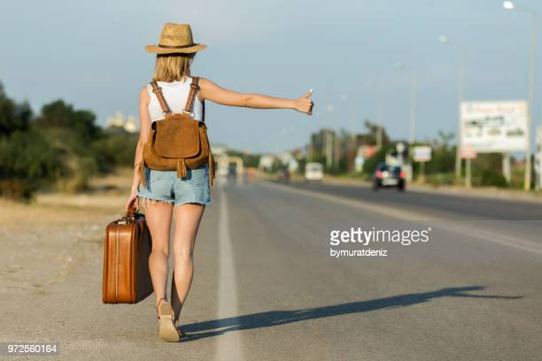 woman hitchhiking on the road trip - hitchhiking stock pictures, royalty-free photos & images