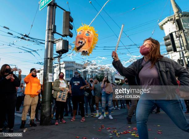 TOPSHOT A woman hits a Donald Trump pinata as people celebrate Joe Biden being elected President of the United States in the Castro district of San...
