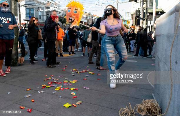 A woman hits a Donald Trump pinata as people celebrate Joe Biden being elected President of the United States in the Castro district of San Francisco...
