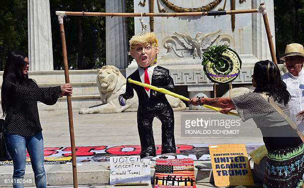 A woman hits a pinata of US Republican presidential candidate Donald Trump during a protest in Mexico City on October 12 2016 / AFP / RONALDO SCHEMIDT