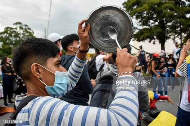 Woman hits a saucepan in protest against the government during the national strike against the tax reform proposed by Duque's administration on April...