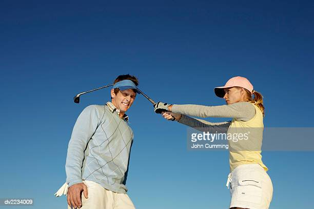woman hitting a man over the head with a golf club - golf humour photos et images de collection