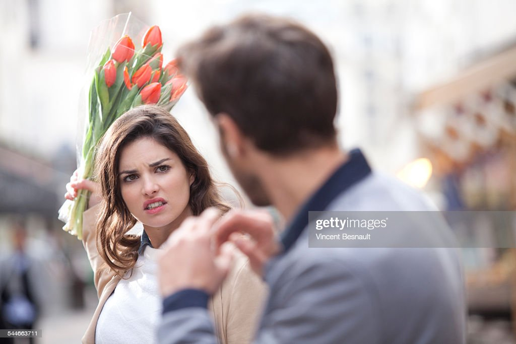 Woman hitting a man with a bouquet of flowers : Stock Photo
