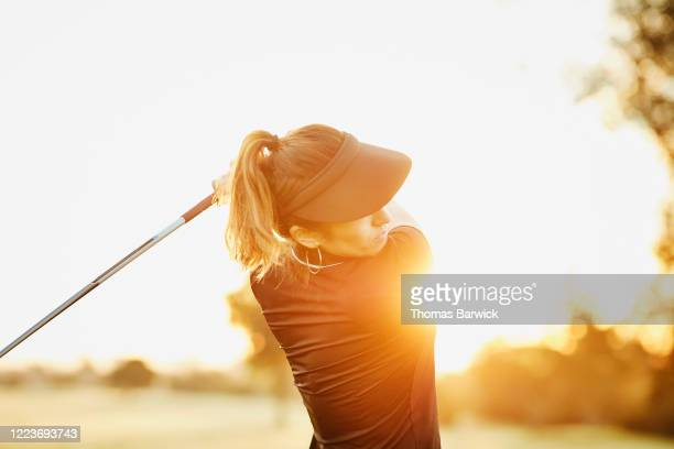 woman hitting drive during early morning round of golf - golf stock pictures, royalty-free photos & images