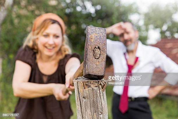 Woman hitting fence post with sledgehammer with exhausted businessman in the background