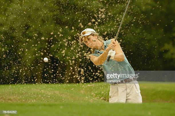 Woman hitting golf ball out of sand trap