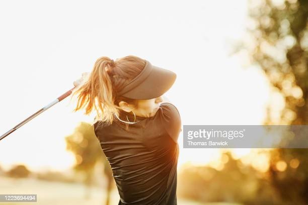 woman hitting shot during early morning round of golf - extra long stock pictures, royalty-free photos & images